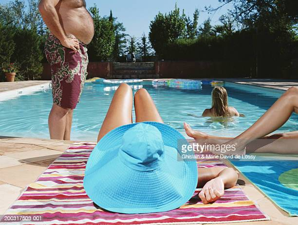 Four people at swimming pool, woman wearing blue sun hat, rear view