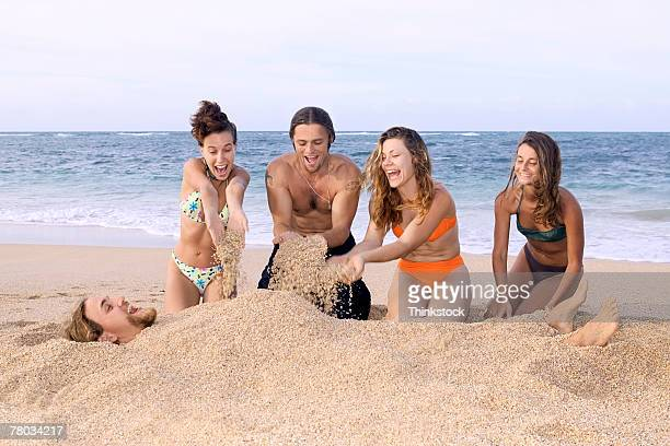 four people bury their friend in the sand at the beach - enterrar imagens e fotografias de stock