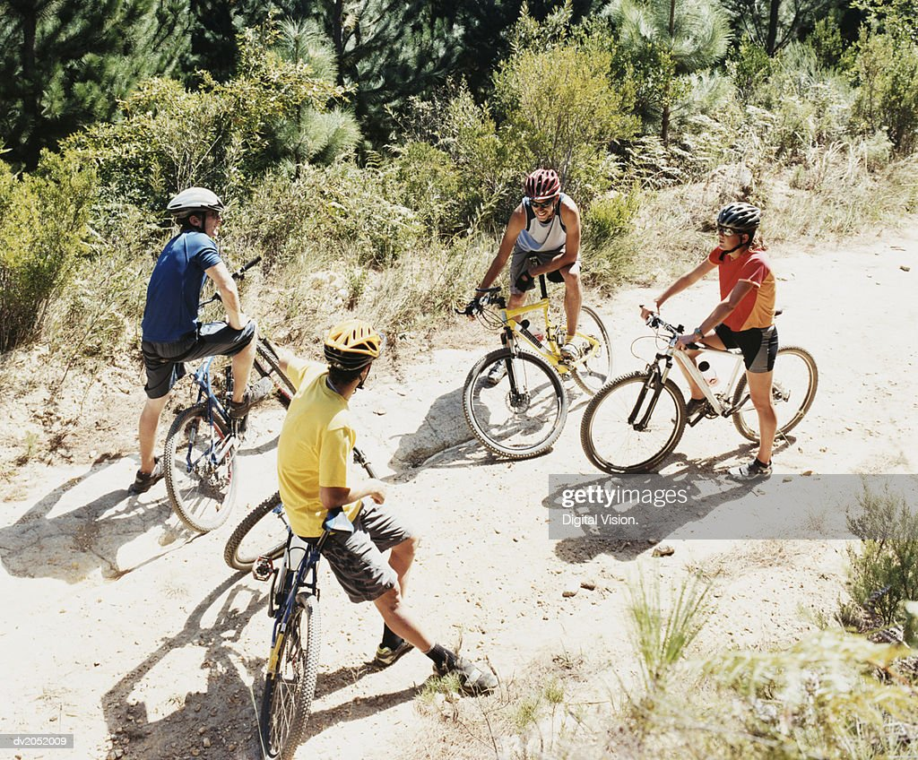 Four People Chatting on a Dirt Road in a Forest Riding Mountain Bikes : Stock Photo