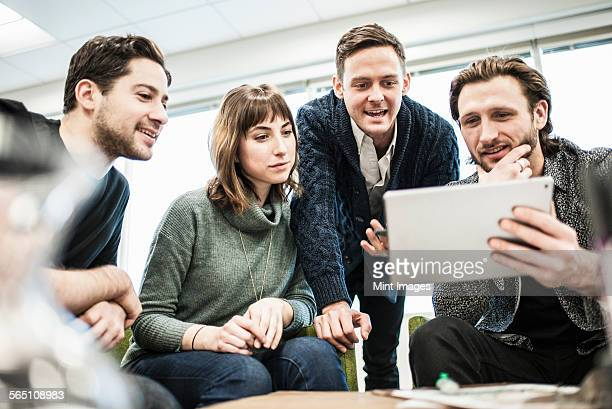 Four people, colleagues at a meeting, and one man sharing a tablet with the group.