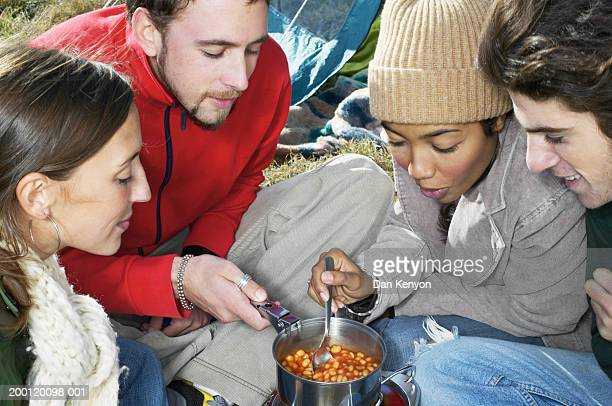 Four people cooking baked beans over camp stove, close-up