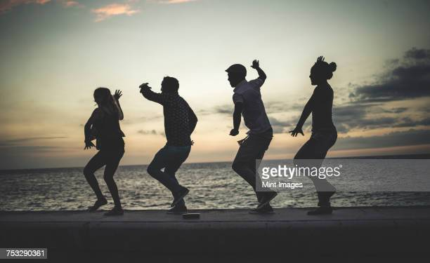 Four people dancing in a line on a sea wall in front of the ocean.