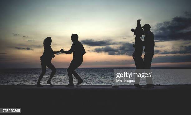 four people dancing on a sea wall in front of the ocean at dusk. - cuba fotografías e imágenes de stock