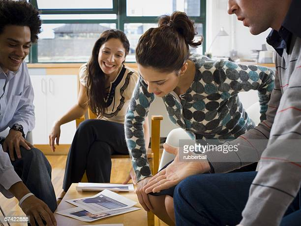 Four people discussing ad layouts