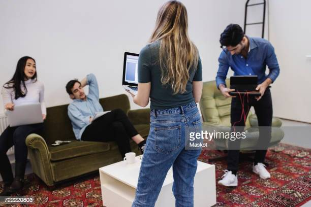 Four people discussing in creative office