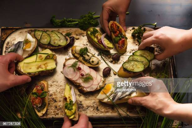 four people eating open sandwiches - appetizer stock pictures, royalty-free photos & images