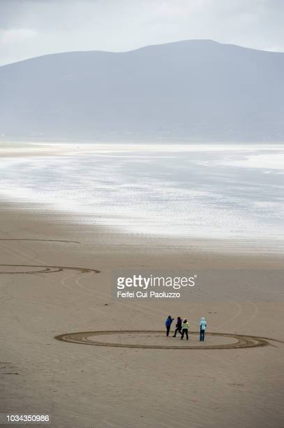 four people enjoying at beach at inch, kerry county, ireland - inch stock pictures, royalty-free photos & images