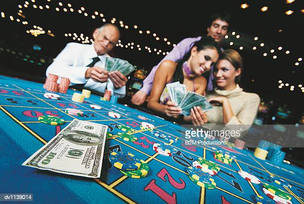 Four People Gambling With Hundred Dollar Banknotes at a Casino Table