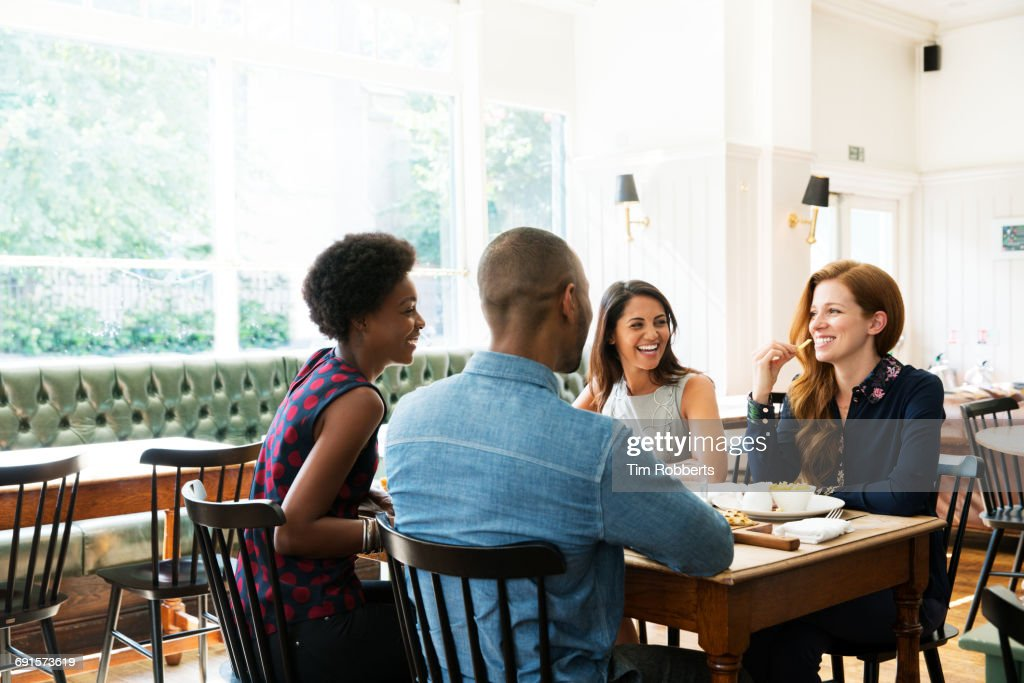 Four People Having Lunch One Eating French Fries Stock Photo