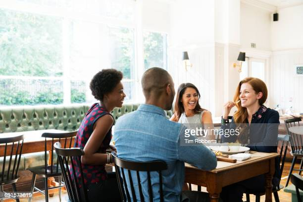 four people having lunch, one eating french fries. - vier personen stockfoto's en -beelden