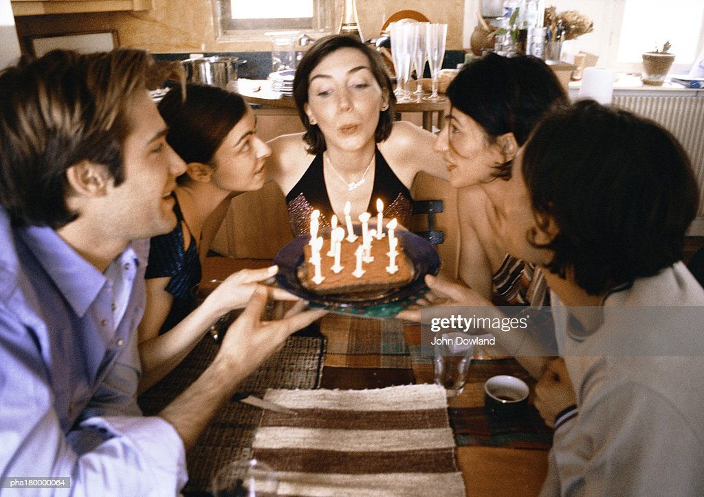Four people holding cake, woman blowing candles : Stockfoto