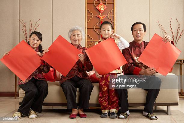 Four people holding posters celebrate Chinese New Year.