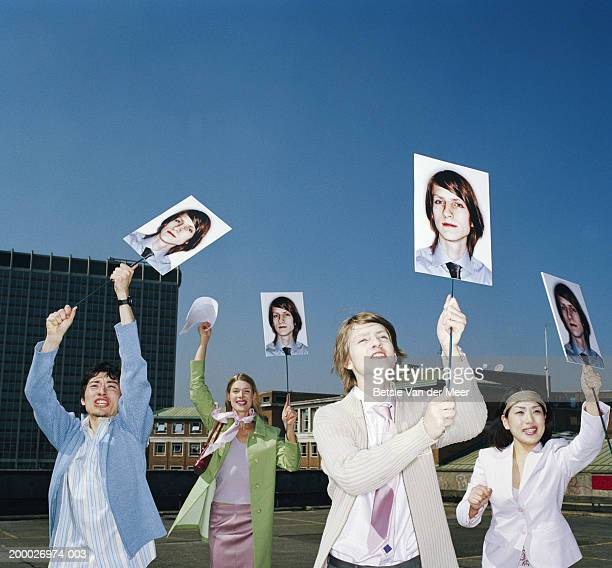 Four people holding up placards bearing identical image of man