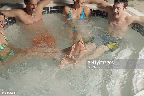 four people in hot tub - playing footsie stock photos and pictures