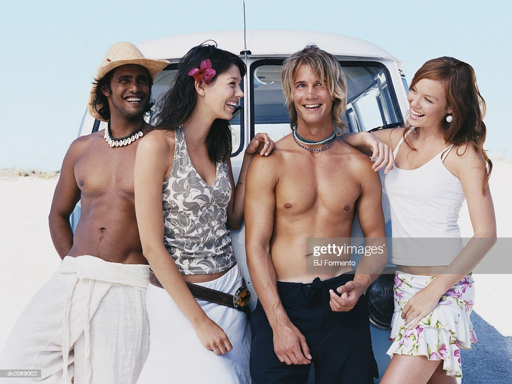 Four People in Summer Outfits Standing in Front of a Camping Van : Stock Photo