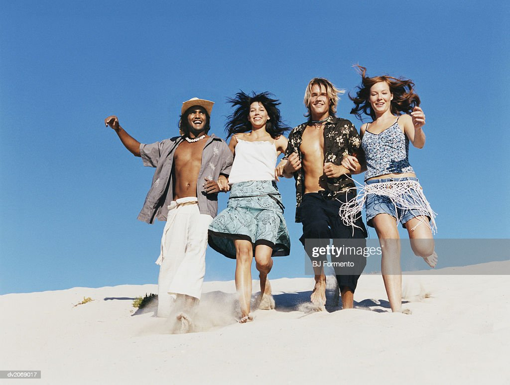 Four people in Summer Outfits Walking Arm in Arm on a Dune : Stock Photo