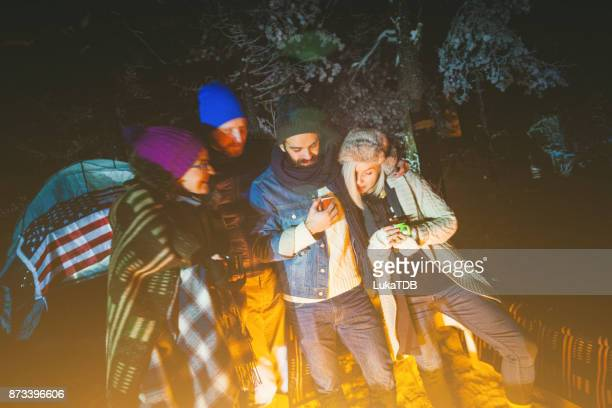 Four people in woodland by night