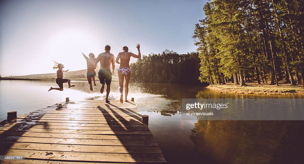 Four people jumping off a jetty into the water : Stock Photo