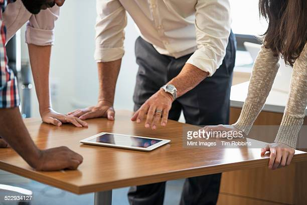 four people leaning on a table at a meeting, looking at a digital tablet. - rolled up sleeves stock pictures, royalty-free photos & images