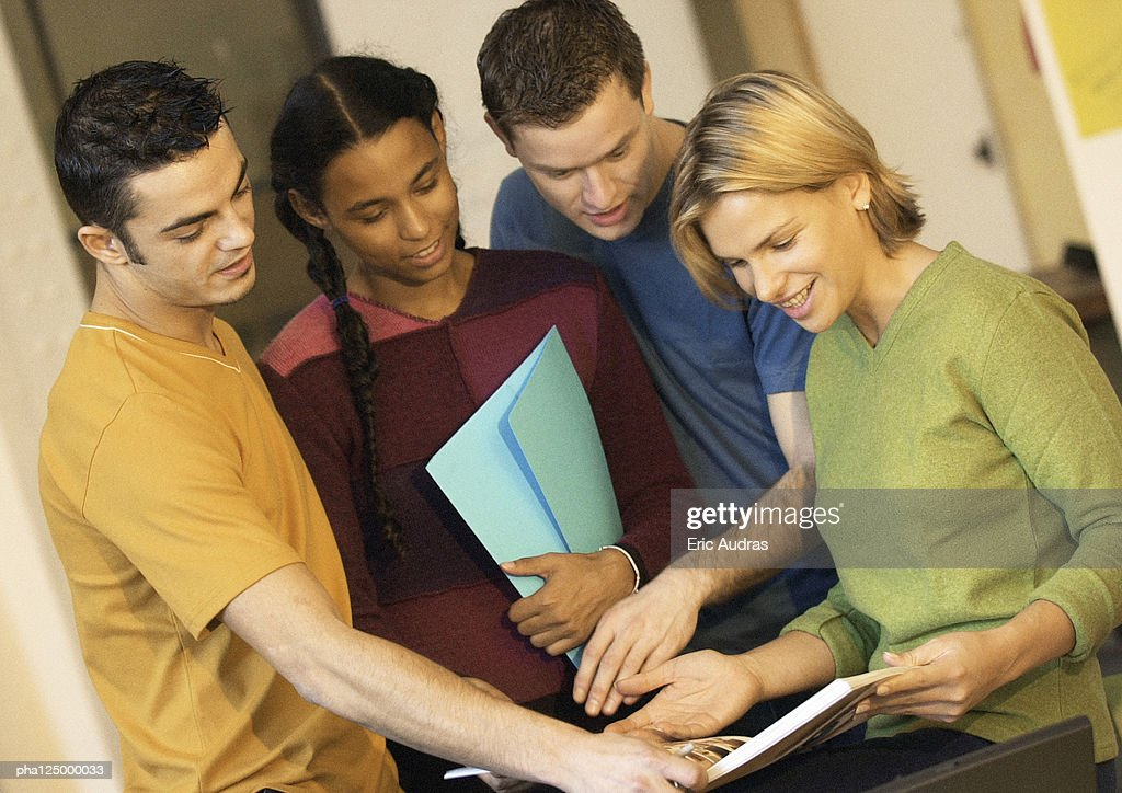 Four people looking at book : Stockfoto
