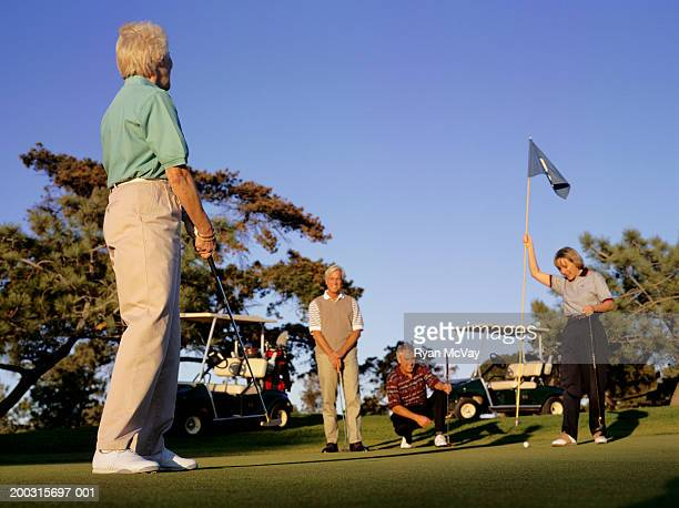 four people on putting green at golf course - 50 59 years stock pictures, royalty-free photos & images