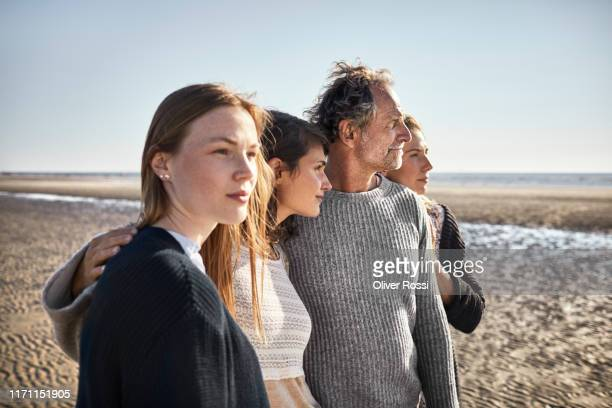 four people on the beach looking away - two generation family stock pictures, royalty-free photos & images