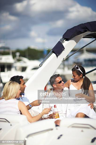 """four people on yacht, drinking and talking - """"compassionate eye"""" fotografías e imágenes de stock"""