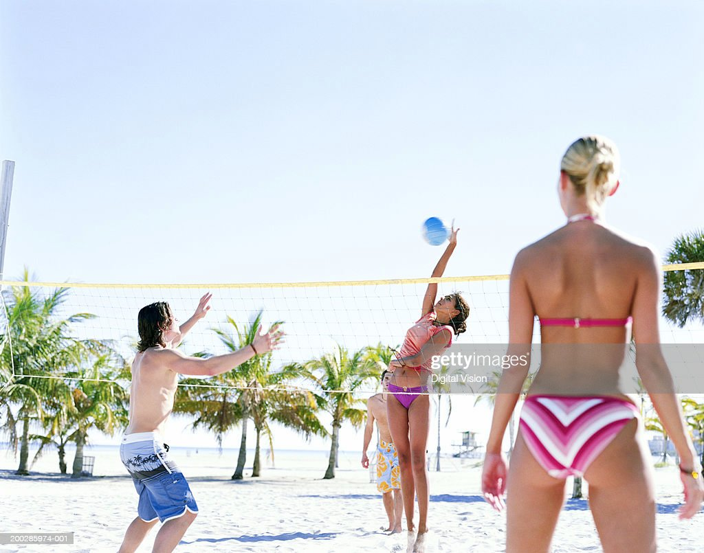 Four people playing volleyball on beach : Stock Photo
