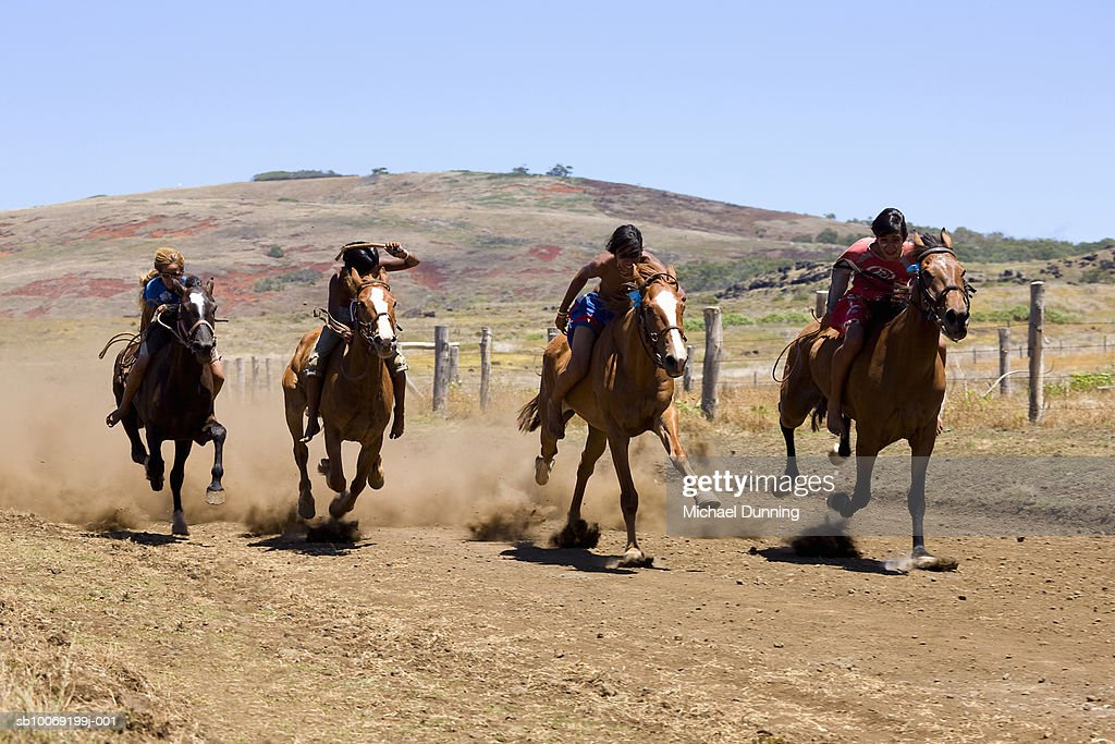 Four people racing on horses in rural setting : Stockfoto