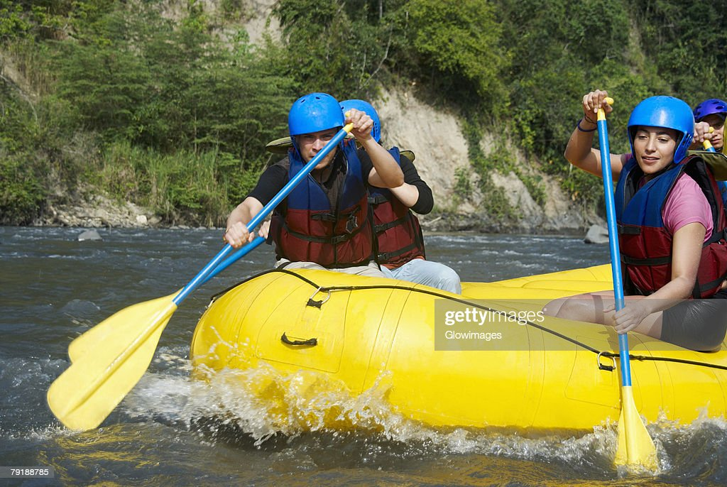 Four people rafting in a river : Stock Photo