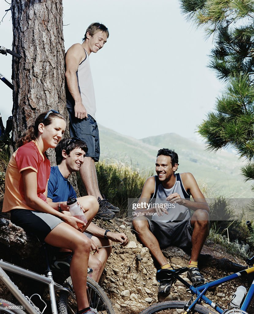 Four People Resting by a Tree Trunk With Their Mountain Bikes : Stock Photo