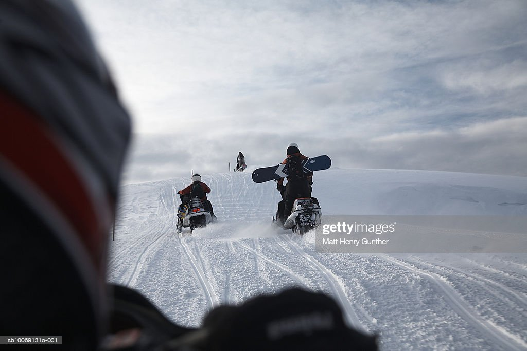 Four people riding on snowmobiles : Stockfoto