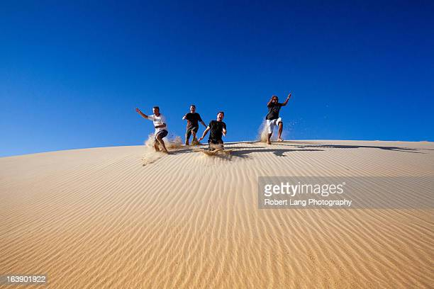 four people running down a sand dune having fun - south australia stock pictures, royalty-free photos & images