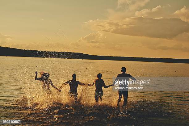 Four people running in the evening waters