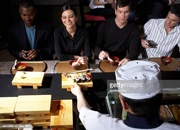 four people sitting at counter in sushi bar, one using mobile phone, waiter in foreground, elevated view - sushi restaurant stock photos and pictures