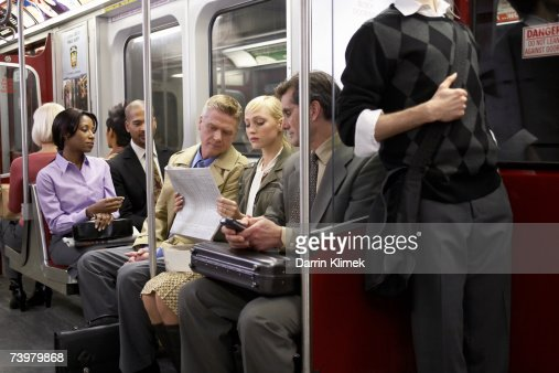 Four People Sitting In Subway Train Woman Reading ...