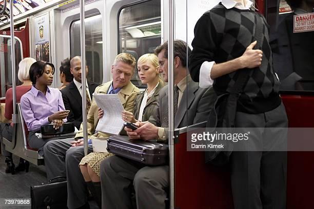 four people sitting in subway train, woman reading newspaper - u bahnzug stock-fotos und bilder