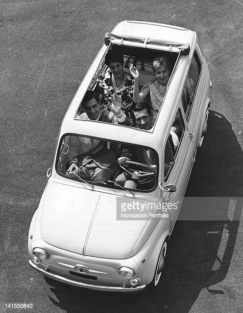 Four people sitting on board car Fiat Giardiniera 500 Italy 1960