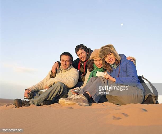 Four people sitting on sand dune, portrait