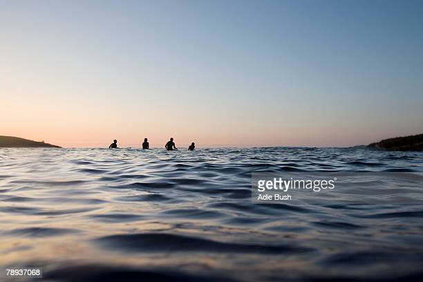 four people sitting on surfboards in the water. - weekend activities stock pictures, royalty-free photos & images