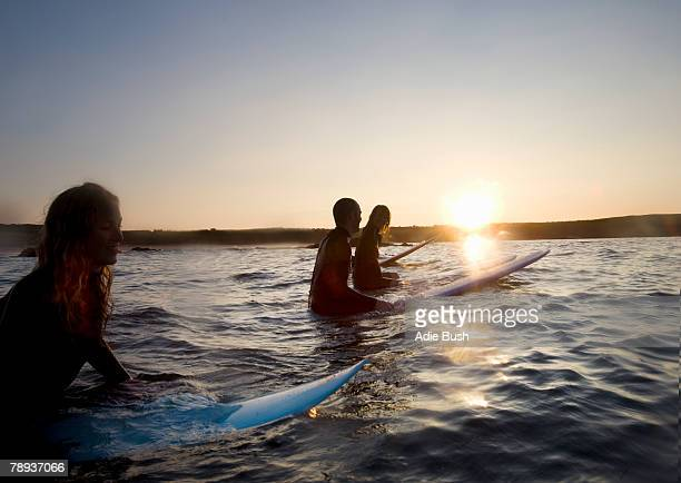 Four people sitting on surfboards in the water smiling.