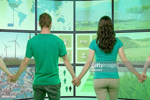 Four people standing, holding hands, in front of graphical screens, displaying environmental images