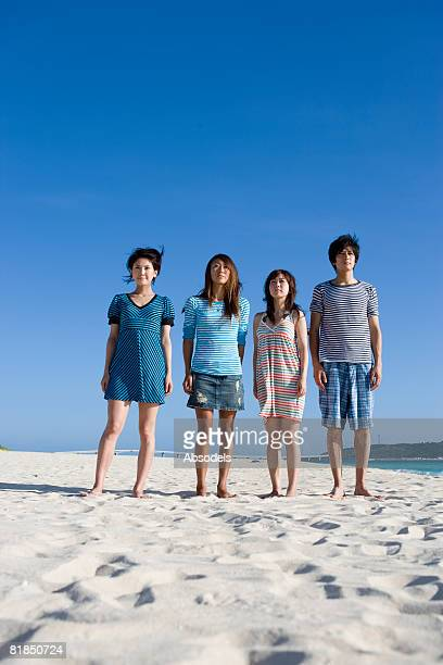 Four people standing on beach, front view