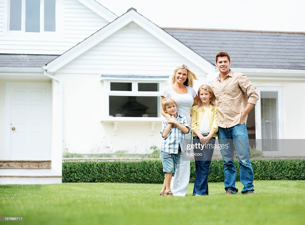 four people standing on lawn in front of their house : Stock Photo