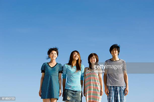Four people standing side by side