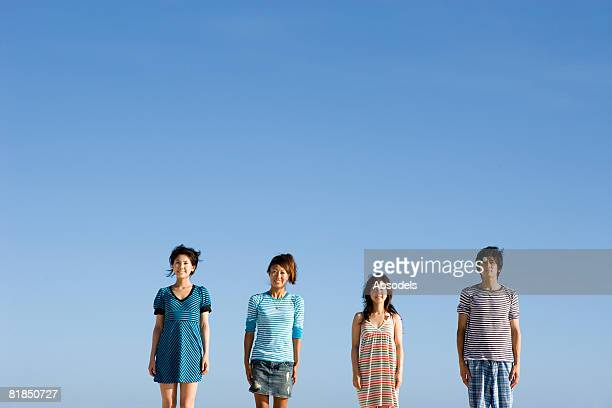 Four people standing strait side by side