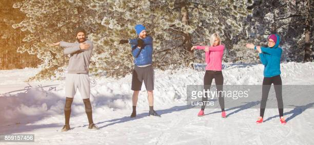 Four people stretching on snow