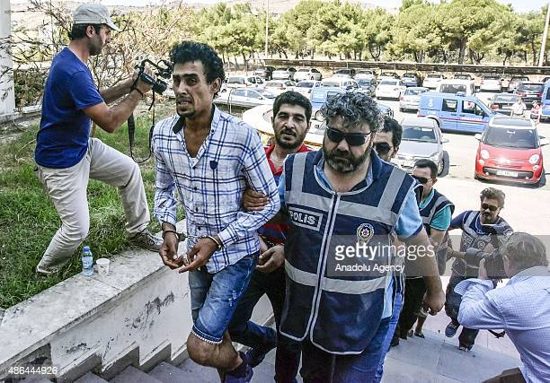 Four people suspected of human trafficking resulting in the death of 12 people are taken to the court in Turkeys southwestern province of Mugla on...