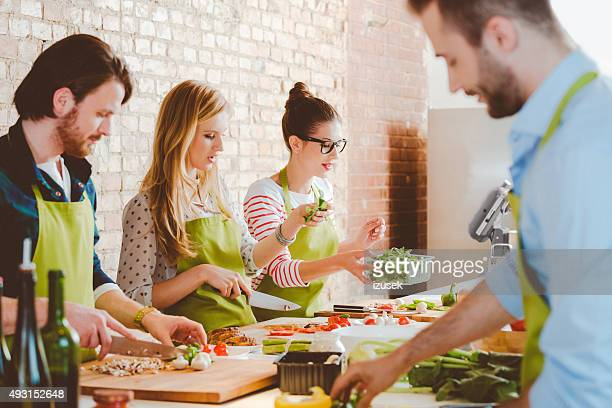 quatre personnes prenant part à un cours de cuisine - food and drink photos et images de collection