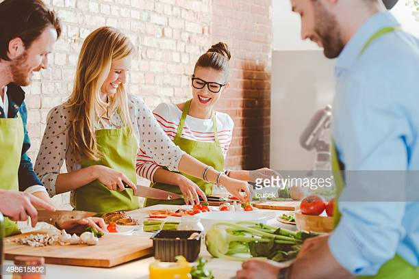 four people taking part in cooking class - werkplaats stockfoto's en -beelden